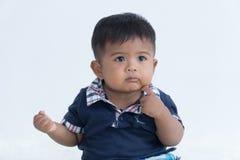 Asiatiskt lite att behandla som ett barn att sitta och att tänka royaltyfri fotografi