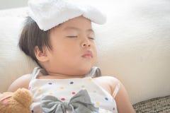 Asiatiskt liten flickasömn och sjukt på soffan med kylare stelnar på henne royaltyfri fotografi