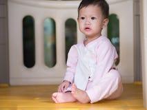 Asiatiskt litet barn som inomhus sitter bort se Arkivfoton