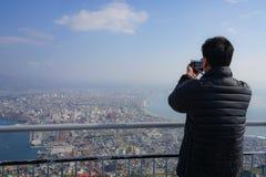 Asiatiskt manligt turist- tagande foto av den Hakodate staden från Mt Hakoda royaltyfri fotografi