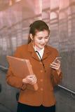 Asiatiskt nätt kvinnainnehavdokument och smart telefon för bruk Fotografering för Bildbyråer