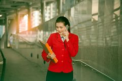Asiatiskt nätt kvinnainnehavdokument och smart telefon för bruk Royaltyfri Fotografi