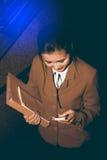 Asiatiskt nätt kvinnainnehavdokument och smart telefon för bruk Royaltyfria Foton