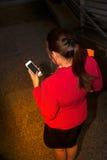 Asiatiskt nätt kvinnainnehavdokument och smart telefon för bruk Arkivfoton