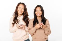 Asiatiskt nätt upphetsat positivt prata för damsystrar royaltyfria bilder