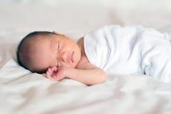 Asiatiskt nyfött behandla som ett barn att sova för pojke Arkivbilder