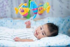 Asiatiskt nyfött behandla som ett barn leende i en säng Fotografering för Bildbyråer