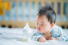 Asiatiskt nyfött behandla som ett barn leende med mjölkar maktflaskan Arkivfoton