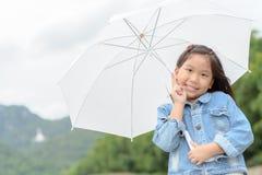 asiatiskt paraply för flickaleende- och innehavvit Royaltyfri Foto