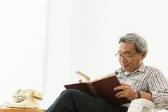 Asiatiskt sammanträde för gamal manexponeringsglasprofessor på den läs- läroboken för stol arkivbilder