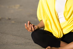 Asiatiskt sammanträde på sand som mediterar bärande guling Arkivfoto
