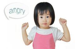 Asiatiskt småbarn som är ilsket, genom att gripa hårt om hennes nävar Royaltyfri Bild