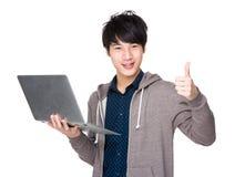 Asiatiskt stiligt manbruk av den bärbar datordatoren och tummen upp Arkivfoton