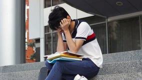 Asiatiskt studentmansammanträde på trappa och läseböcker stock video