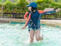 Asiatiskt syskon som k?r och jagar i simbass?ng royaltyfria bilder