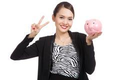 Asiatiskt tecken för seger för show för affärskvinna med svinmyntbanken Royaltyfria Bilder