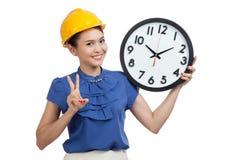Asiatiskt tecken för seger för teknikerkvinnashow med en klocka Arkivfoto