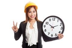 Asiatiskt tecken för seger för teknikerkvinnashow med en klocka Royaltyfri Bild