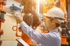 Asiatiskt teknikerunderhåll som kontrollerar tekniska data av pumpen för vatten för kondensator för systemutrustning och tryckmät royaltyfria foton
