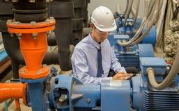 Asiatiskt teknikerunderhåll som kontrollerar tekniska data av pumpen för vatten för kondensator för systemutrustning och tryckmät fotografering för bildbyråer