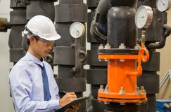 Asiatiskt teknikerunderhåll som kontrollerar tekniska data av pumpen för vatten för kondensator för systemutrustning och tryckmät arkivfoton