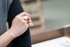 Asiatiskt thailändskt - kinesisk flicka med pärlan och den röda hjärtacirkeln på hennes finger royaltyfria foton