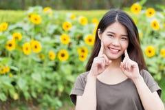 Asiatiskt thailändskt tonårigt leende för gullig stående med solrosen royaltyfria foton