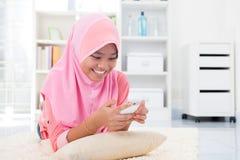 Asiatiskt tonårigt smsa ett meddelande Arkivfoto