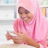 Asiatiskt tonårigt smsa på telefonen Arkivbilder
