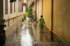 Asiatiskt tonårigt vänta på monsunregnet för att stoppa arkivbild