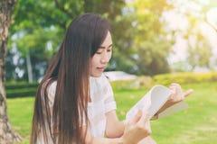 Asiatiskt tunt tonårigt kopplar av läsning i gräsplanen parkerar arkivbilder