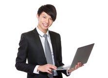 Asiatiskt ungt affärsmanbruk av anteckningsbokdatoren Arkivfoton