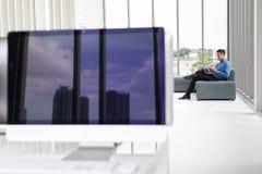 Asiatiskt ungt affärsmansammanträde på soffan med bärbar datordatoren och royaltyfria bilder