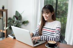 Asiats-Geschäftsfrau der neuen Generation, die Laptop an der Kaffeestube verwendet stockfotografie