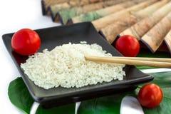Asiatuppsättning av ris, tomater, pinnar, grönt blad och trans. Royaltyfri Fotografi