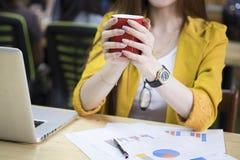 Asien affärskvinna i regeringsställning som rymmer den röda koppen kaffe Royaltyfri Foto