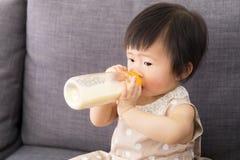 Asien-Baby, das mit Milchflasche einzieht stockfoto