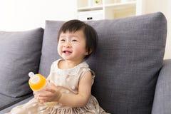 Asien behandla som ett barn flickan som innehavet mjölkar flaskan arkivfoton