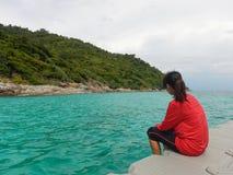 Asien-Frau, die das rote Hemd sitzt auf Plastikfloss und dem Schauen trägt lizenzfreies stockfoto