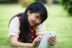 Asien-Frau, die Tablette verwendet stockfotografie
