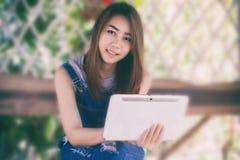Asien-Frauen, die Tablette an im Freien für verwenden, entspannen sich Zeit stockfotografie