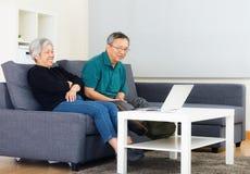 Asien gamla par som håller ögonen på på datoren Arkivbild