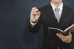 Asien-Geschäftsmann, der bookand Stift hält und auf leerer Wand für denkt Stockbild