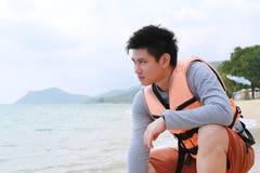 Asien-gutaussehender Mann, der auf Strand geht Stockfotografie
