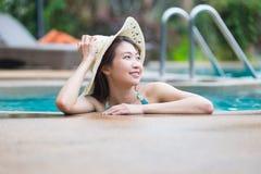Asien härlig kvinna och stor hatt som kopplar av på simbassäng Arkivfoto