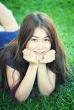 Asien härlig le kvinna som ligger på gräs Arkivfoton