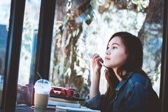 Asien-Jugendsitzen, wenn es allein mit denkt, machen eine Anmerkung im Café Lizenzfreies Stockfoto