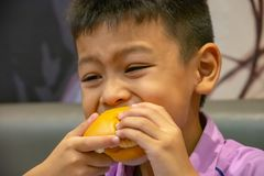Asien-Junge der Hamburgerfische in der Hand, der das Essen hält stockfoto