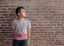 Asien-Jungenstandvorderseite-Ziegelsteinhohes alter Stockfotografie