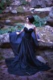 Asien kvinna i svart långt klänninganseende på skog Arkivbilder
